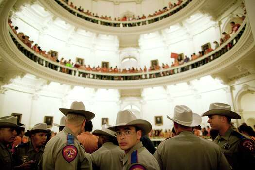 Texas State Troopers block the entrance to the State Capitol rotunda after abortion rights advocates filled it to capacity in Austin, Texas on Friday night, July 12, 2013. Republicans in the Texas Legislature passed an omnibus abortion bill that is one of the most restrictive in the nation, but Democrats vowed Saturday to fight in the courts and at the ballot box as they used the measure to rally their supporters. More than 2,000 demonstrators filled the Capitol building in Austin to voice their opposition to the bill, including six protesters who were dragged out of the Senate chamber by state troopers for trying to disrupt the debate. The Republican majority passed the bill unchanged just before midnight, with all but one Democrat voting against it. Photo: Tamir Kalifa, Associated Press / FR170773 AP