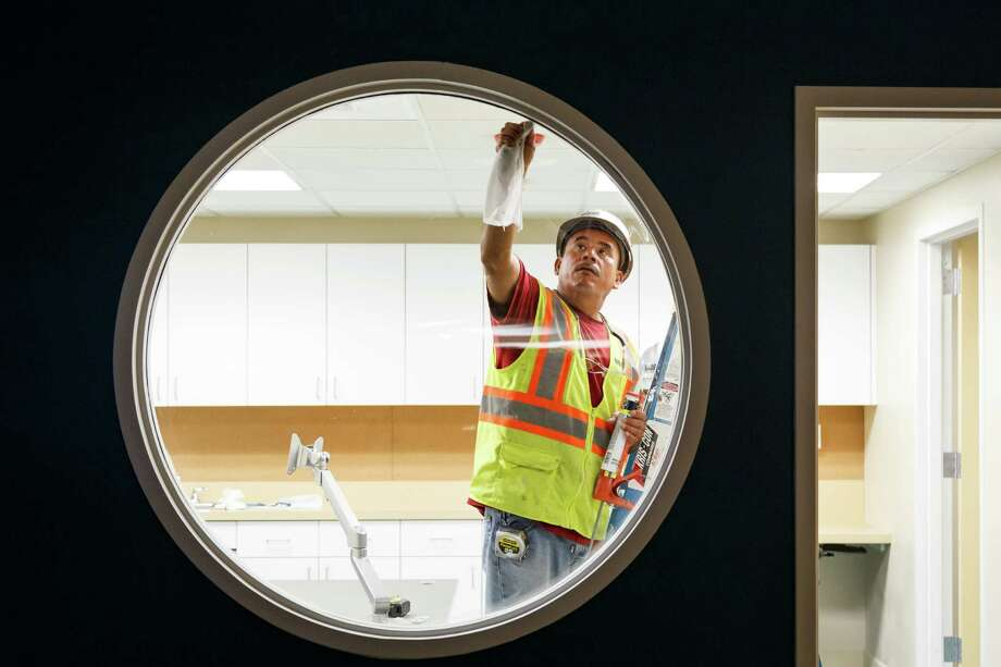 "A construction worker puts the finishing touches on the newly remodeled children's department on the first floor of the 109-year-old Rosenberg Library, Monday, July 8, 2013, in Galveston.  In 2008, Hurricane Ike's massive storm surge wiped out the first floor of Galveston's Rosenberg Library, laying waste to the entire children's section, ""Every book, every poster, every puppet -- gone,"" said Karen Stanley, head of children's services.  The library, which was built in 1904 and enjoys the distinction of being the oldest public library in Texas in continuous operation, unveils its new children's section on July 17. Photo: Michael Paulsen, Houston Chronicle / © 2013 Houston Chronicle"