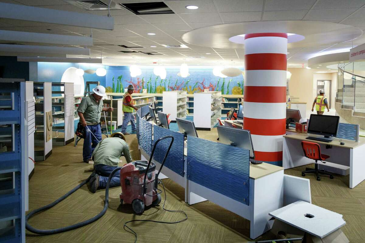 Construction workers put the finishing touches on the newly remodeled children's department on the first floor of the 109-year-old Rosenberg Library, Monday, July 8, 2013, in Galveston.