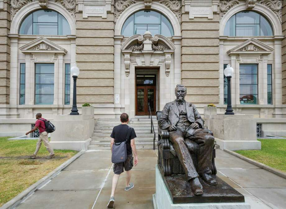 Visitors walk into the 109-year-old Rosenberg Library and past a bronze life-size sculpture of Henry Rosenberg a Swiss immigrant who settled in Galveston in 1843 and became a successful businessman, Monday, July 8, 2013, in Galveston. Photo: Michael Paulsen, Houston Chronicle / © 2013 Houston Chronicle