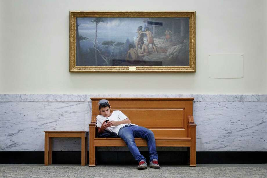 Kaleb Patten, 14, uses the free wireless access on his phone at the 109-year-old Rosenberg Library, Monday, July 8, 2013, in Galveston. Photo: Michael Paulsen, Houston Chronicle / © 2013 Houston Chronicle