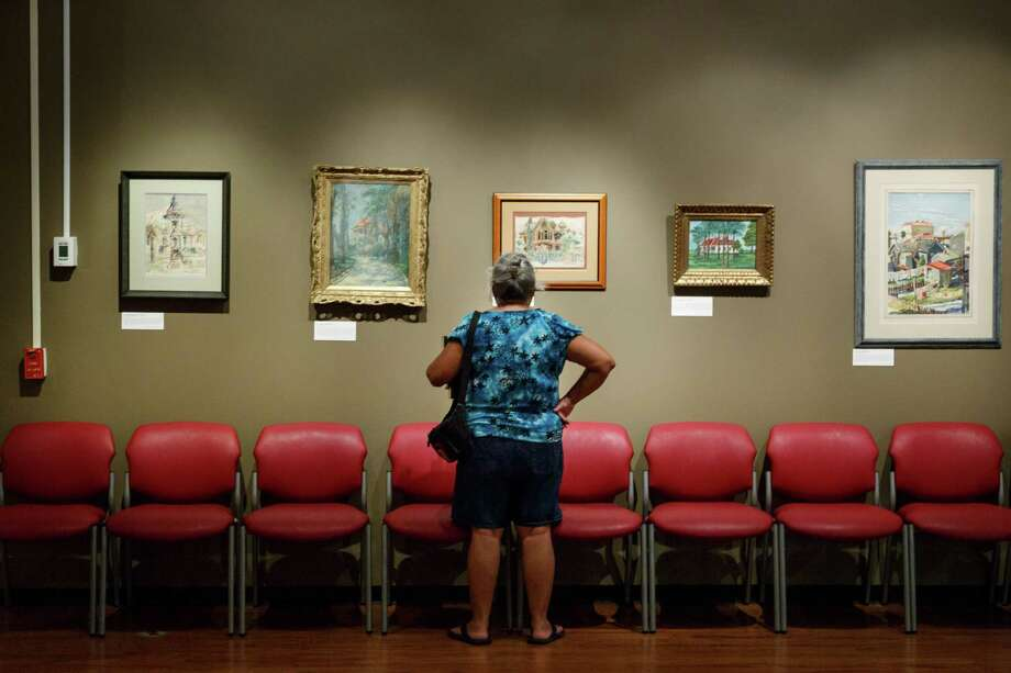 "A woman looks at paintings in the from the exhibit ""Island Art / Island Architecture: Paintings of Historic Galveston Homes"" in the Harris Gallery at the Rosenberg Library Museum, Monday, July 8, 2013, in Galveston. Photo: Michael Paulsen, Houston Chronicle / © 2013 Houston Chronicle"