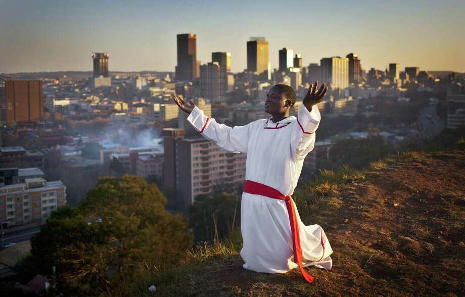 A worshipper prays on a hilltop overlooking Johannesburg. On Friday, Nelson Mandela's wife said the former South African president is responding to treatment. Photo: Ben Curtis / Associated Press