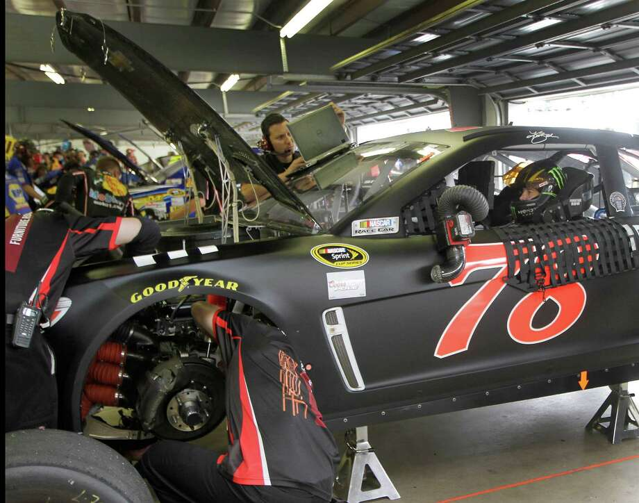 Kurt Busch sits in his car as his crew puts on final touches during the final practice before Sunday's NASCAR Sprint Cup auto race at New Hampshire Motor Speedway, Saturday, July 13, 2013 in Loudon, N.H. (AP Photo/Jim Cole) ORG XMIT: NHMS101 Photo: Jim Cole / AP