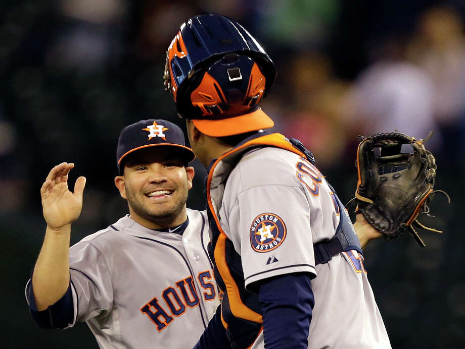 Second baseman Jose Altuve, left, has been a spark plug on a rebuilding team with its fair share of veterans like catcher Carlos Corporan. Photo: Ted S. Warren, STF / AP