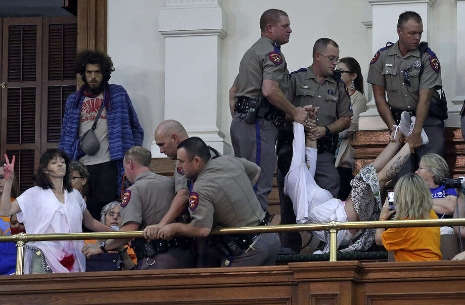 Protesters who tried to chain themselves to a rail are removed from the Senate gallery by DPS troopers. Photo: Tom Reel / San Antonio Express-News
