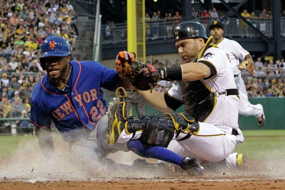 Pittsburgh Pirates catcher Russell Martin (55) holds on to the ball after tagging out New York Mets' Eric Young Jr. (22), who attempted to score from third on an infield grounder by David Wright to third baseman Pedro Alvarez, right rear, during the fifth inning of a baseball game in Pittsburgh on Saturday, July 13, 2013. (AP Photo/Gene J. Puskar) ORG XMIT: PAGP103 Photo: Gene J. Puskar / AP