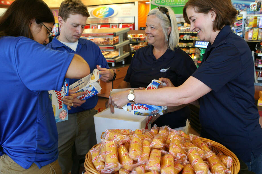 Liz Garcia (left), Corey Mowen, Judy Gleason and Shelly Faris put Twinkies into a cooler Saturday so the  treats could be handed out free at the gas pumps of the Corner Store on UTSA Boulevard off of I-10. Twinkies officially will return to Corner Store shelves Monday. Photo: Cynthia Esparza / For The San Antonio Express-News