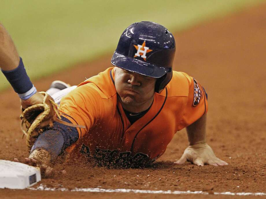 Astros second baseman Jose Altuve is tagged out by the Rays' James Loney while diving back to first base during the fifth inning Saturday. Altuve finished 1 for 4 and scored a run. Photo: Scott Iskowitz / Associated Press
