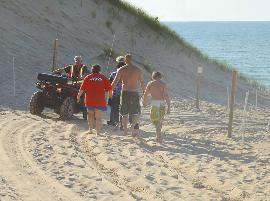 Family members of the boy buried in a sand dune in Indiana were escorted to the beach by a police chaplain Friday evening as heavy equipment was brought in to assist in the rescue. Photo: Julie McClure / Michigan City News Dispatch