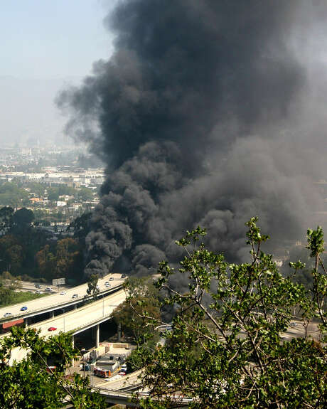 Smoke billows from the fire that erupted after a tanker truck flipped and spilled its load of gasoline in Los Angeles. Photo: Steve Karman / Associated Press