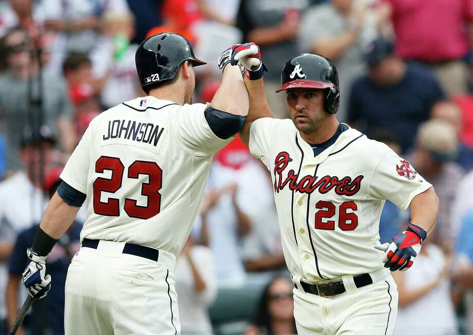 Atlanta's Dan Uggla (right) is congratulated by Chris Johnson after his solo homer in the seventh. Photo: Kevin C. Cox / Getty Images
