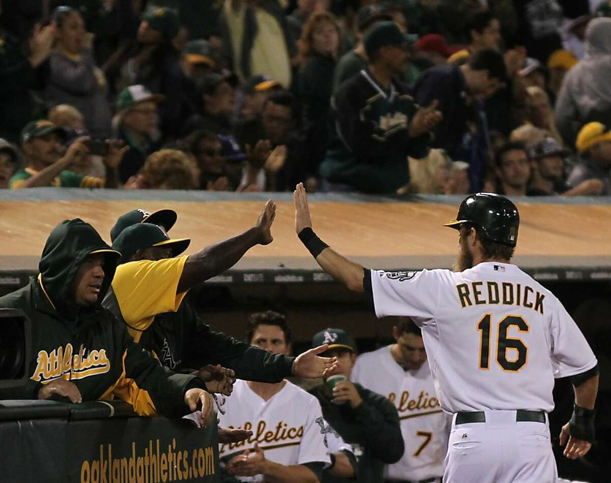 Oakland Athletics Josh Reddick is greeted at the dugout after scoring on a RBI single by Coco Crisp in the 7th inning of their MLB baseball game with the Boston Red Sox Saturday, July 13, 2013, In Oakland CA.