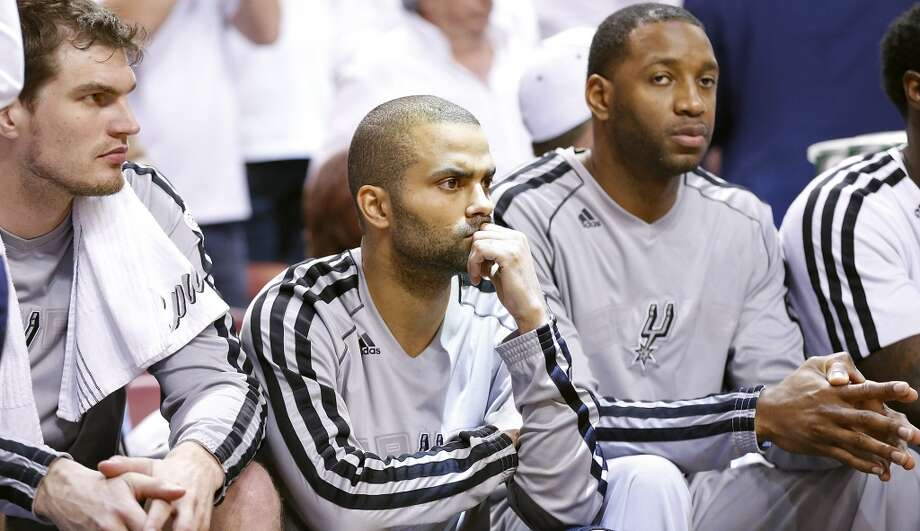 San Antonio Spurs' Tiago Splitter, San Antonio Spurs' Tony Parker, and San Antonio Spurs' Tracy McGrady sit on the bench during the second half of Game 7 of the 2013 NBA Finals against the Miami Heat Thursday, June 20, 2013 at American Airlines Arena in Miami. (Edward A. Ornelas/San Antonio Express-News)