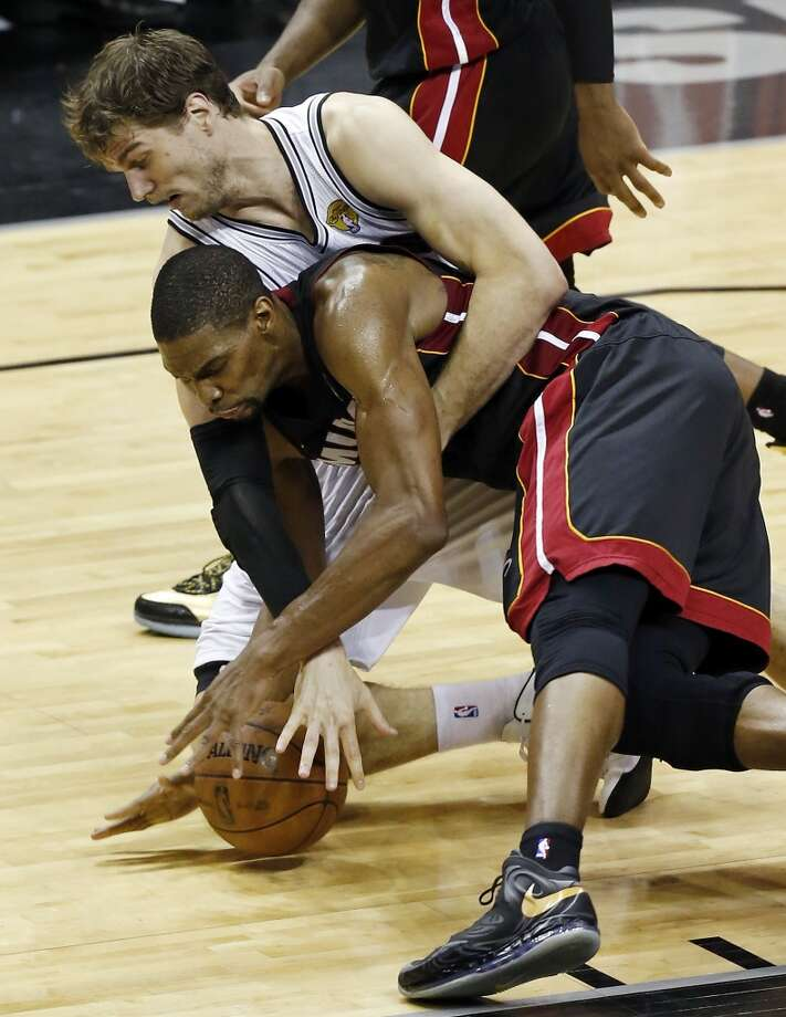 San Antonio Spurs' Tiago Splitter and Miami Heat's Chris Bosh grab for a loose ball during first half action in Game 5 of the 2013 NBA Finals Sunday June 16, 2013 at the AT&T Center. (Edward A. Ornelas/San Antonio Express-News)