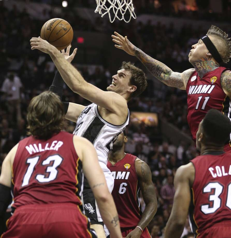 San Antonio Spurs' Tiago Splitter drives through four Miami defenders during the first half of Game 3 of the NBA Finals at the AT&T Center on Tue., June 11, 2013.