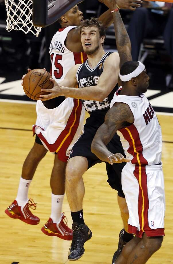 San Antonio Spurs' Tiago Splitter drives to the basket between Miami Heat's Mario Chalmers and Miami Heat's LeBron James during first half action in Game 1 of the 2013 NBA Finals Thursday June 6, 2013 at American Airlines Arena in Miami, Fla.
