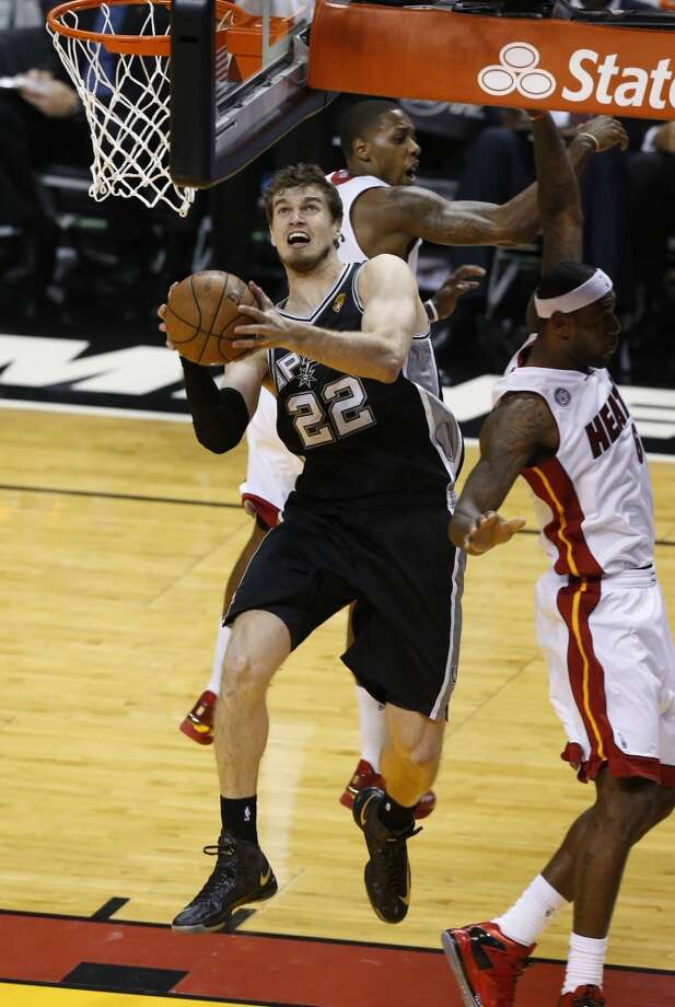 Spurs' Tiago Splitter drives for a shot against Miami Heats' Mario Chalmers and LeBron James (right) during Game 1 of the 2013 NBA Finals Thursday June 6, 2013 at American Airlines Arena in Miami, Fla.