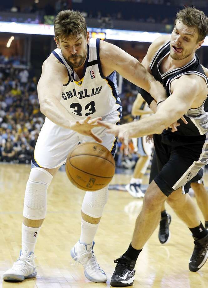 Memphis Grizzlies' Marc Gasol and San Antonio Spurs' Tiago Splitter grab for a loose ball during second half action in Game 3 of the 2013 Western Conference finals Saturday May 25, 2013 at the FedEx Forum in Memphis, Tenn. The Spurs won 104-93 in overtime.