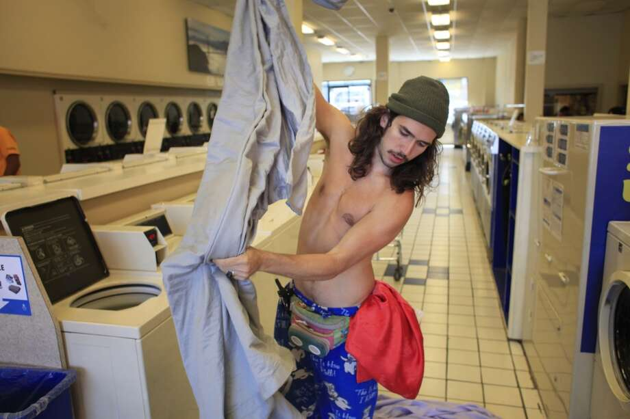 "Preparing for a cuddle event, Travis ""Topless Travis"" Sigley  does laundry near his home in San Francisco."