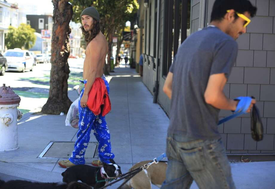 "After running errands, Travis ""Topless Travis"" Sigley   walks home in San Francisco."