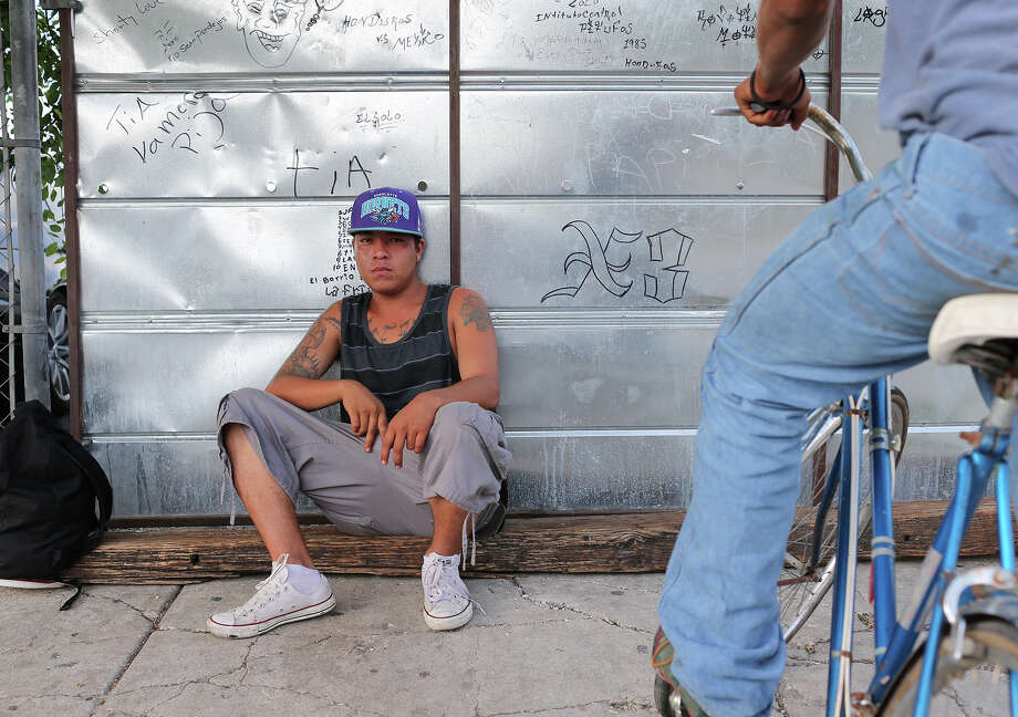 A man going by the name of Cris Juan, 23, hangs out at the corner of West Travis Street and North Frio Street, Tuesday, June 25, 2013. VIA Metropolitan Transit is attempting to buy up the properties in the block between North Medina, West Travis, North Frio and West Houston Streets for a transportation hub. A homeless and transient population inhabits the area. Photo: JERRY LARA, San Antonio Express-News / © 2013 San Antonio Express-News