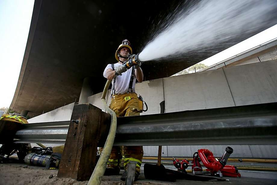A Los Angeles Fire Department firefighter sprays firefighting foam into a freeway tunnel after a tanker truck flipped, spilled its load of gasoline and caught fire, snarling traffic for miles, Saturday, July 13, 2013 near downtown Los Angeles. (AP Photo/Los Angeles Times, Luis Sinco) Photo: Luis Sinco, Associated Press