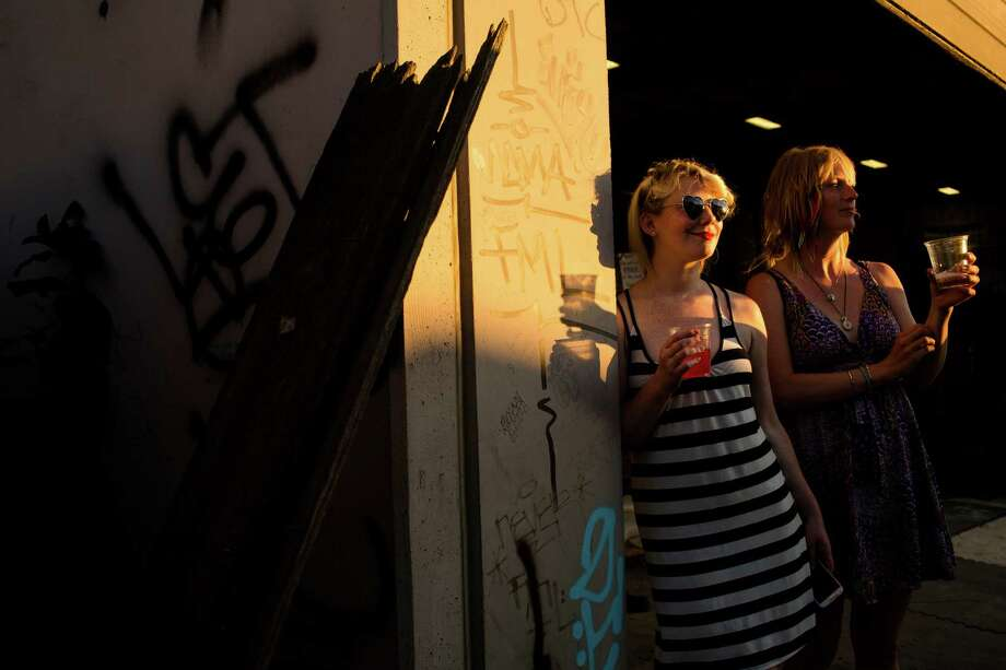 In a wash of golden evening light, Kristin Kangur, center right, and Allison Lee, right, relax with drinks during Sub Pop's Silver Jubilee Saturday, July 13, 2013, in the Georgetown neighborhood of Seattle. The free event commemorated 25 years of existence for the Seattle-local label. Photo: JORDAN STEAD, SEATTLEPI.COM / SEATTLEPI.COM