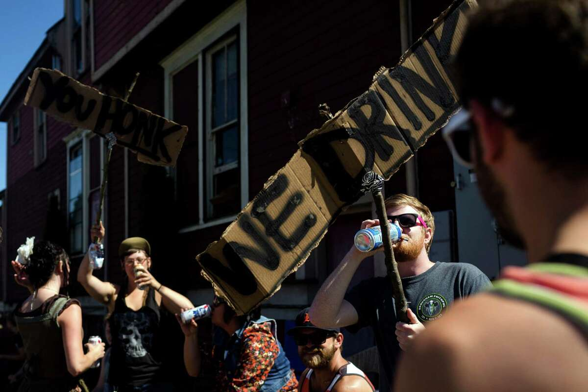 A group of attendees proclaim their love for drinking and encourage nearby drivers to honk outside of Sub Pop's Silver Jubilee Saturday, July 13, 2013, in the Georgetown neighborhood of Seattle. The free event commemorated 25 years of existence for the Seattle-local label.