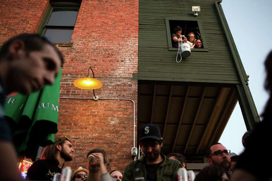 Women lower a bucket down into the bar below during Sub Pop's Silver Jubilee Saturday, July 13, 2013, in the Georgetown neighborhood of Seattle. The free event commemorated 25 years of existence for the Seattle-local label. Photo: JORDAN STEAD, SEATTLEPI.COM / SEATTLEPI.COM