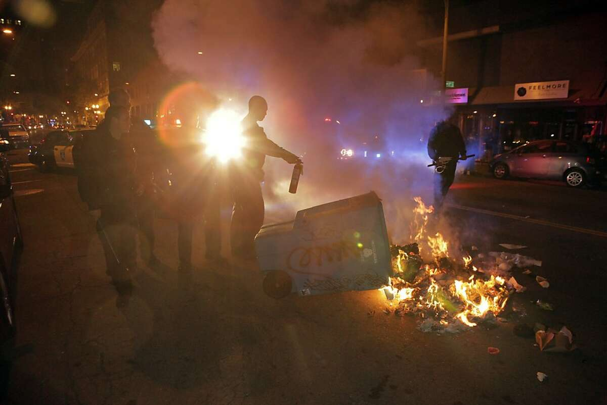 Oakland Police Officers try to extinguish a garbage can fire on Telegraph Avenue after protesters set fires and vandalized stores in downtown Oakland, Calif., on Saturday, July 13, 2013, after the acquittal of George Zimmerman in the death of Trayvon Martin earlier in the day.