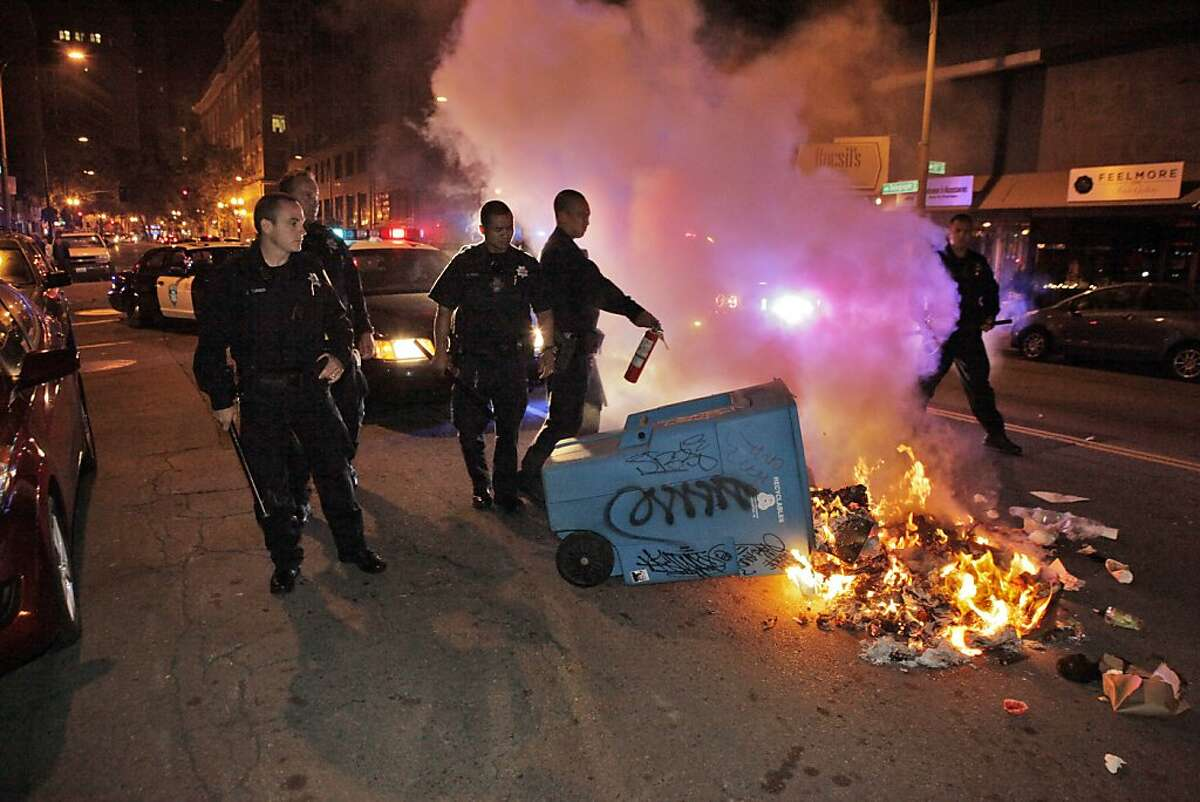 Oakland Police Officers try to extinguish a garbage can fire on Telegraph Avenue after protesters set fires and vandalized stores in downtown Oakland after the acquittal of George Zimmerman in the death of Trayvon Martin earlier in the day.