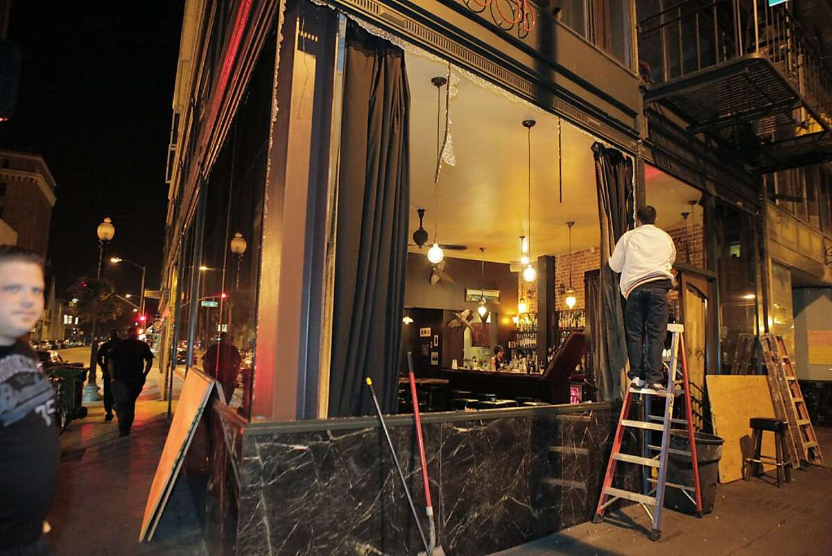 A worker removes the smashed out windows at Dogwood on Telegraph Avenue after protesters set fires and vandalized stores in downtown Oakland on Saturday after the acquittal of George Zimmerman in the death of Trayvon Martin earlier in the day in Florida.