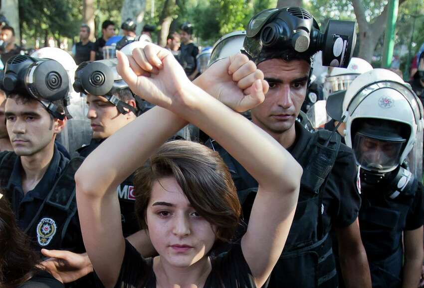 A woman holds her arms crossed as riot police pushes people out of Gezi park in Istanbul, Turkey, Monday, July 8, 2013. An Istanbul park that was at the center of weeks of anti-government demonstrations opened for a few hours Monday, but Turkish authorities quickly closed it and fired a water canons, tear gas and rubber bullets at protesters heading to the area for a planned rally.