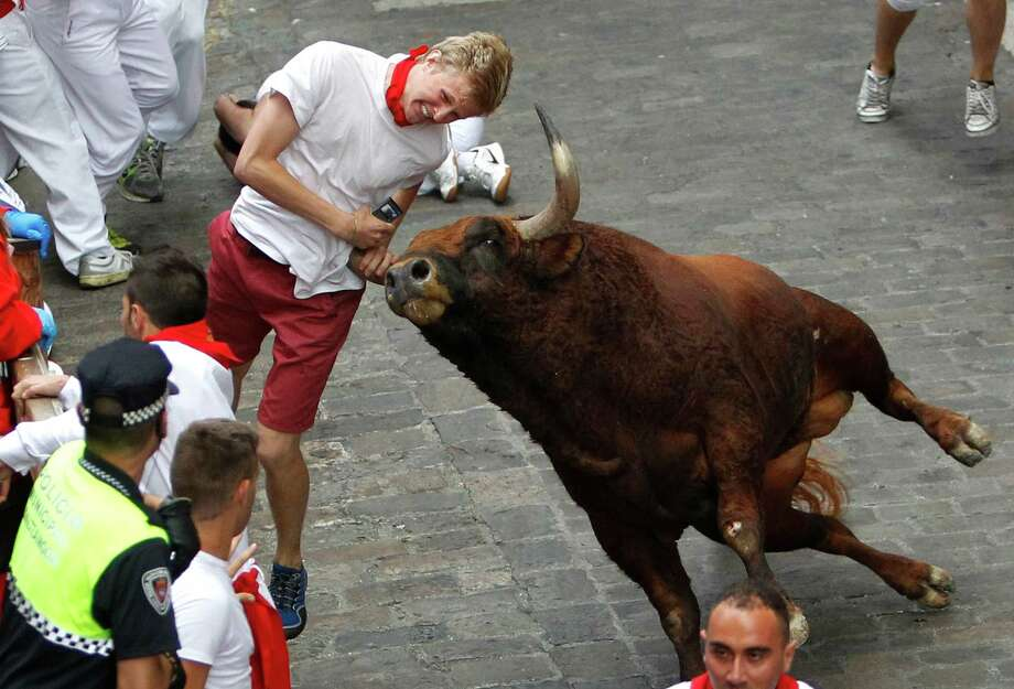 "A runner is gored by an ""El Pilar"" fighting bull during the running of the bulls at the San Fermin festival, in Pamplona, Spain, Friday, July 12, 2013. An American and two Spaniards were gored Friday. Photo: AP"