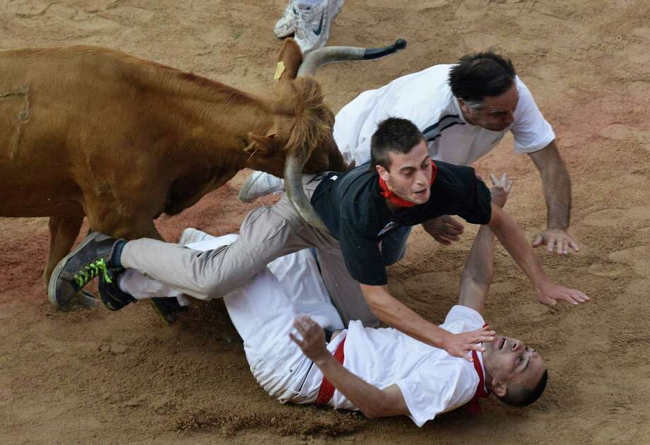 "Revelers are pushed over by a bull at the end of the last running of the bulls at the San Fermin festival, in Pamplona Spain on Sunday, July 14, 2013. Revelers from around the world arrive to Pamplona every year to take part in some of the eight days of the running of the bulls glorified by Ernest Hemingway's 1926 novel ""The Sun Also Rises."" Photo: AP"