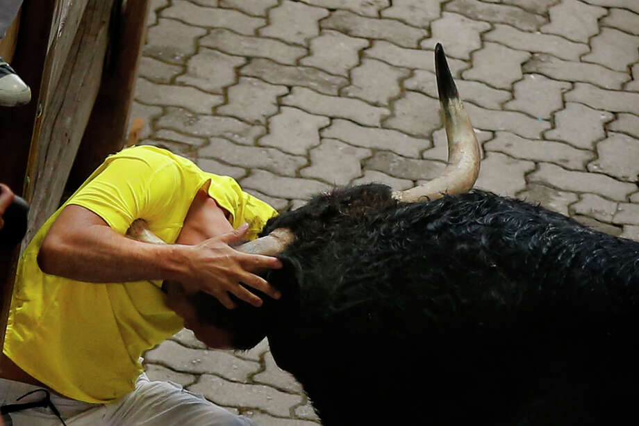 An 'El Pilar' fighting bull gores a reveler during the running of the bulls of the San Fermin festival, in Pamplona, Spain, Friday, July 12, 2013. Photo: AP