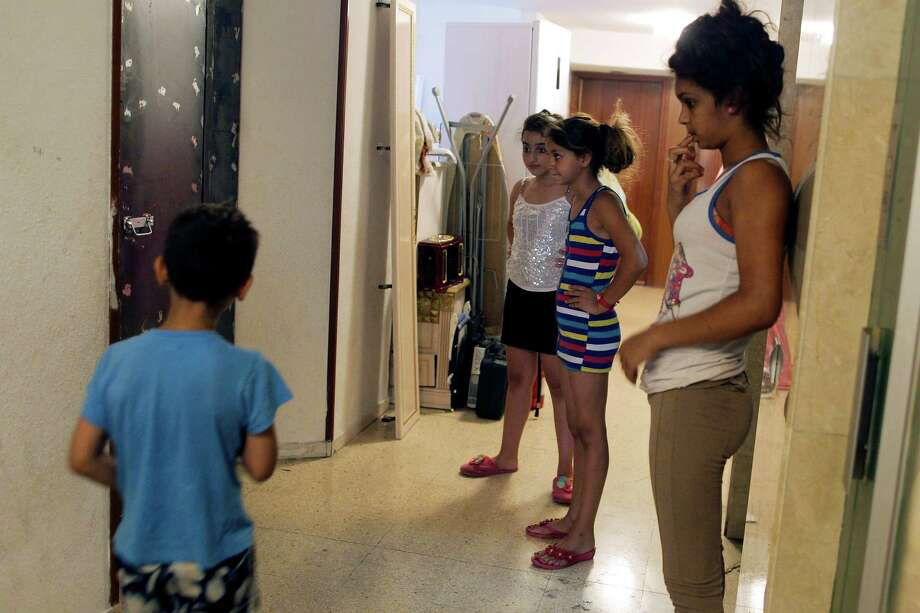 Felix Gimenez Silva's son, left, looks at his apartment's welded door after he and his family were evicted by the police in Madrid, Spain, Friday, July 12, 2013. His father Felix Gimenez Silva is unemployed, receives state help, and collects and sells metal for living. He lives with his wife Florentina Silva Montoya and 6 more members, 4 of them children, in a City Hall Housing Company (EMVS) apartment for the past 25 years. They have paid the rent which they have previously failed to pay but the City Hall Housing Company (EMVS) still proceeded with their eviction. Photo: AP