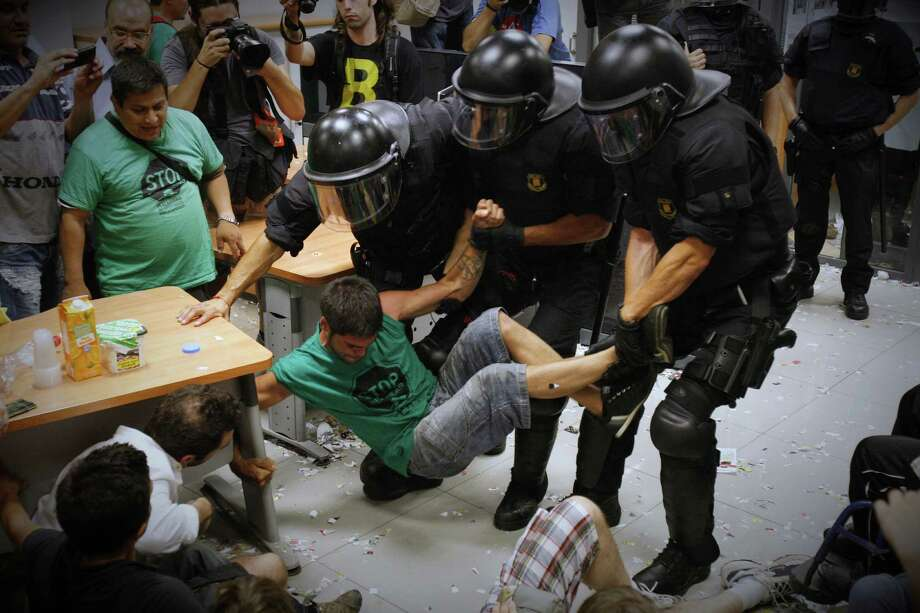 An activist of Mortgage Victims' Platform (PAH) is carried away by riot police officers after occupying a bank as part of a protest to support a neighbor who is facing an eviction process in Barcelona, Spain, Thursday July 11, 2013. With 26 percent unemployment, Spain is struggling to emerge from its second recession in just over three years as the economy battles to recover from the collapse of its once-booming real estate sector. Photo: AP