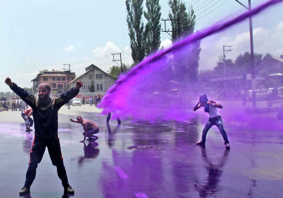 Police uses colored water to disperse Kashmiri government employees during a protest in Srinagar, India, Monday, July 8, 2013. Police detained dozens of government employees during the protest demanding regularization of contractual jobs and a hike in salary. Photo: AP