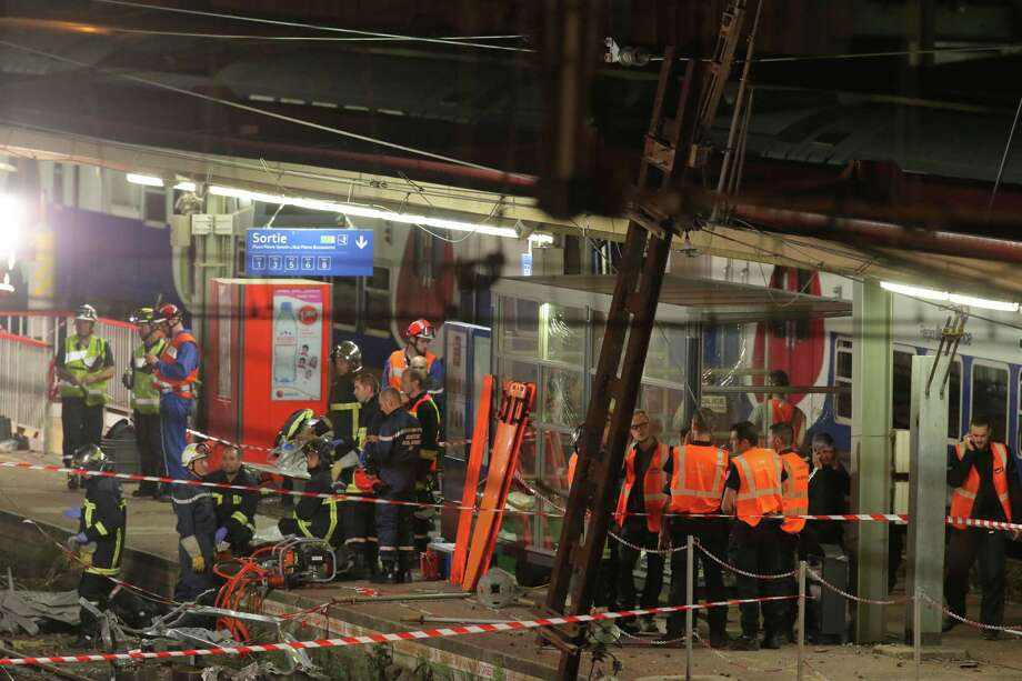 Rescue workers stand at the scene where a train derailed at a station in Bretigny sur Orge, south of Paris, Saturday, July 13, 2013. A packed passenger train skidded off its rails after leaving Paris on Friday, leaving seven people believed dead and dozens injured as train cars slammed into each other and overturned, authorities said. (AP Photo/Michel Euler). Photo: AP