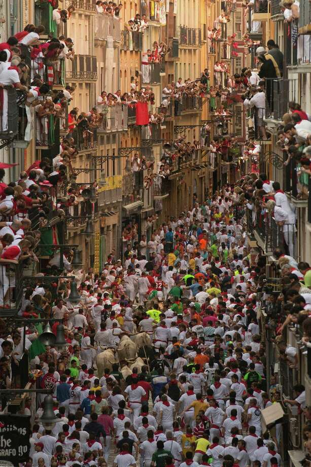 "CORRECTS DATE - Runners make their way through the Estafeta street with ""Miura"" fighting bulls as people watch them from their balconies during the running of the bulls of the San Fermin festival, in Pamplona, Spain, Sunday, July 14, 2013. Revelers from around the world arrive to Pamplona every year to take part on some of the eight days of the running of the bulls glorified by Ernest Hemingway's 1926 novel ""The Sun Also Rises."" Photo: AP"