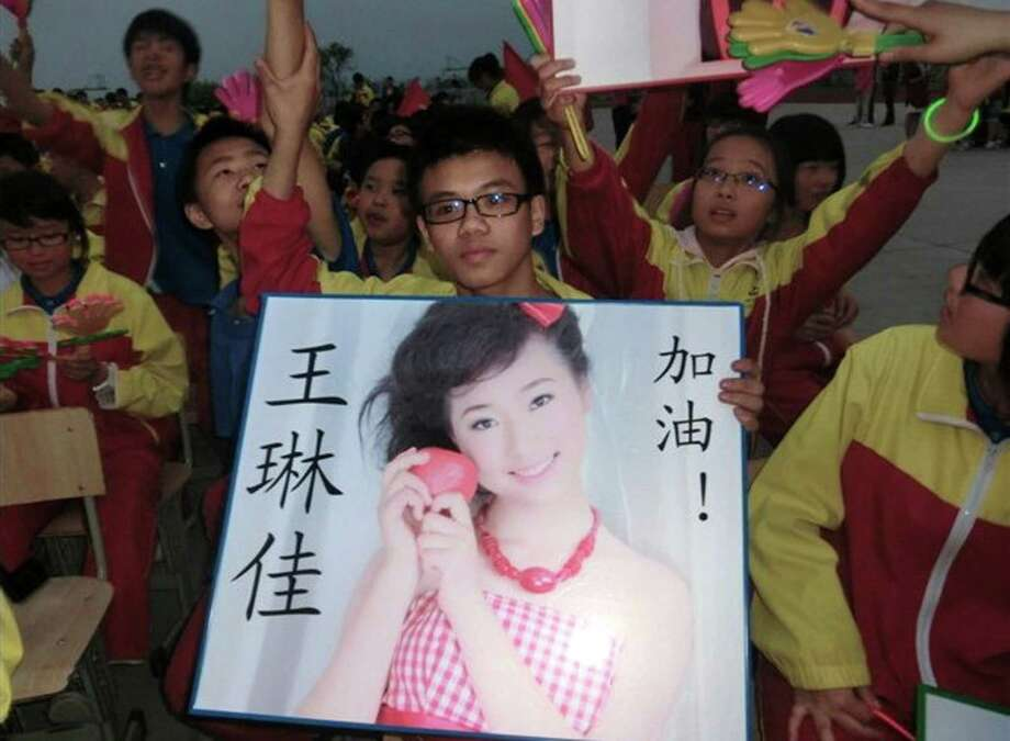 In this undated photo made available Monday, July 8, 2013, a supporter of Wang Linjia, holds up a photo of her with her name during a talent show at a school in Jiangshan city in eastern China's Zhejiang province. Chinese state media and Asiana Airlines have identified the two victims of the Asiana Airlines crash at San Francisco International Airport girls as Ye Mengyuan and Wang Linjia, students in Zhejiang, an affluent coastal province in eastern China.  (AP Photo) Photo: AP