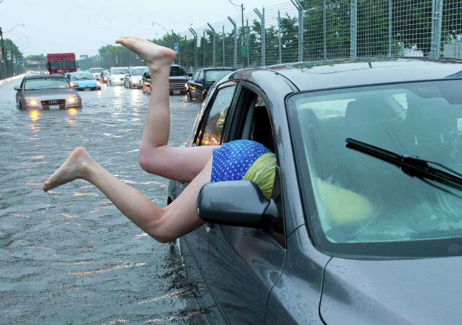 A woman gets back into her flooded car on the Toronto Indy course on Lakeshore Boulevard in Toronto on Monday, July 8 2013. Photo: AP