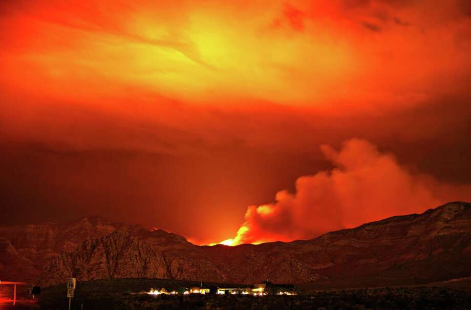 The Carpenter 1 fire burns in the mountains behind the Red Rock Conservation Area visitor center near Las Vegas early in the morning of Thursday, July 11, 2013. The fire has forced the closure of the Red Rock National Conservation Area Scenic Loop. Firefighters in the mountains near Las Vegas hoped Thursday that predicted rain showers and cooler temperatures would help them corral the massive wildfire that for 10 days charred almost 44 square miles and was still just 15 percent contained. Photo: AP