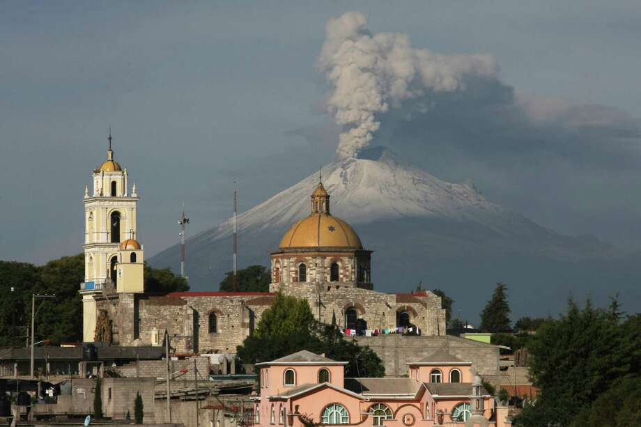 The main church in the town of San Damian Texoloc, Mexico stands in front of the Popocatepetl volcano as is spews ash and vapor early Tuesday, July 9, 2013. Last Saturday, Mexico's National Center for Disaster Prevention raised the volcano alert from Stage 2 Yellow to Stage 3 Yellow, the final step before a Red alert, when possible evacuations could be ordered after the Popocatepetl volcano spit out a cloud of ash and vapor 2 miles (3 kilometers) high over several days of eruptions. Photo: AP