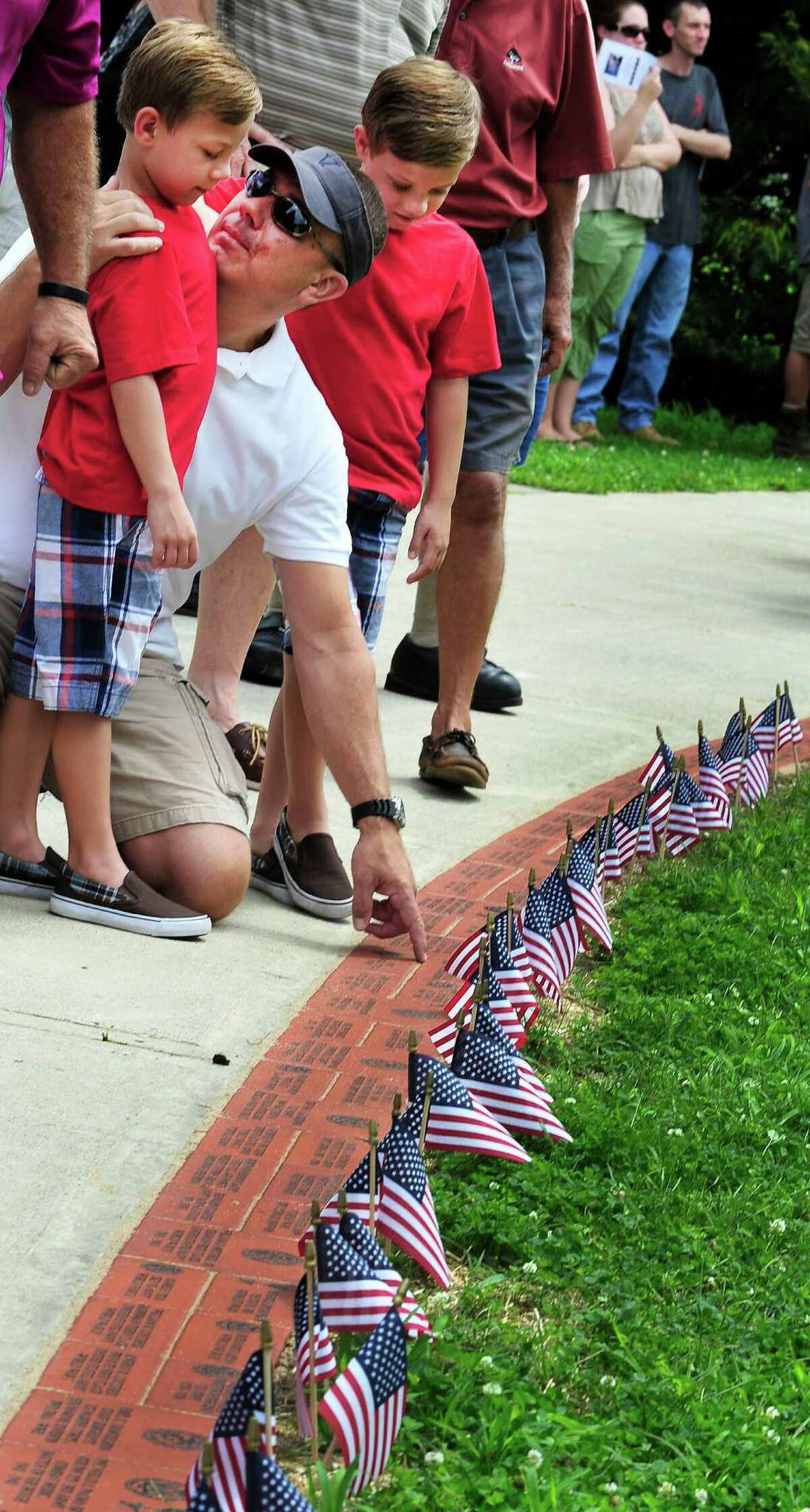 Phil Colla, of Brookfield, points out the brick honoring his grandfather to his twin sons, Michael, left, and P.J., both 6, as the Veterans Walkway of Honor dedication ceremony takes place at the Danbury War Memorial, in Danbury, Conn. Sunday, July 14, 2013.