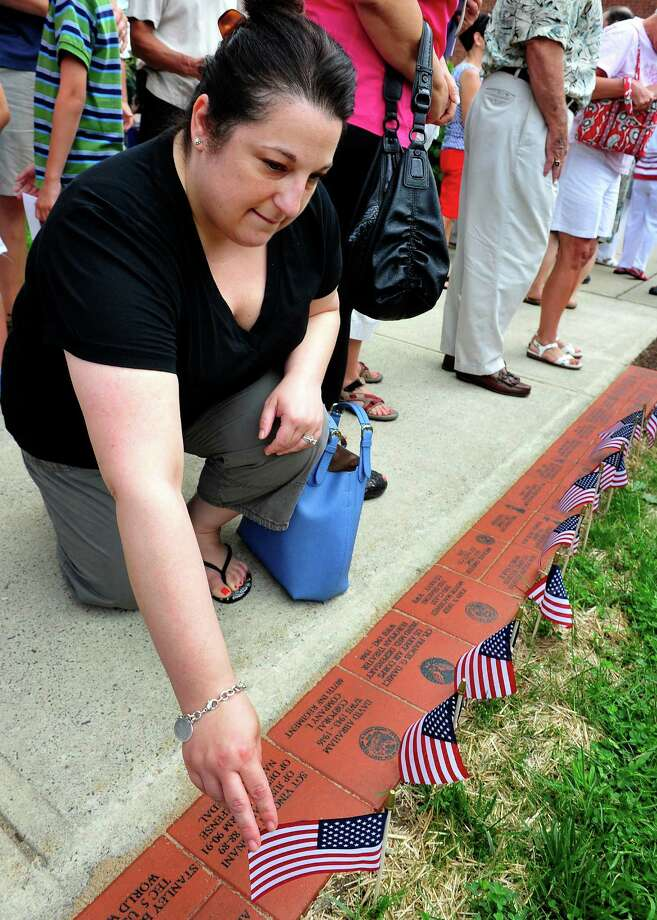 Amy Fagnani, of Danbury, visits the the bricks honoring her husband and two grandfathers, as the Veterans Walkway of Honor dedication ceremony takes place at the Danbury War Memorial, in Danbury, Conn. Sunday, July 14, 2013. Photo: Michael Duffy / The News-Times