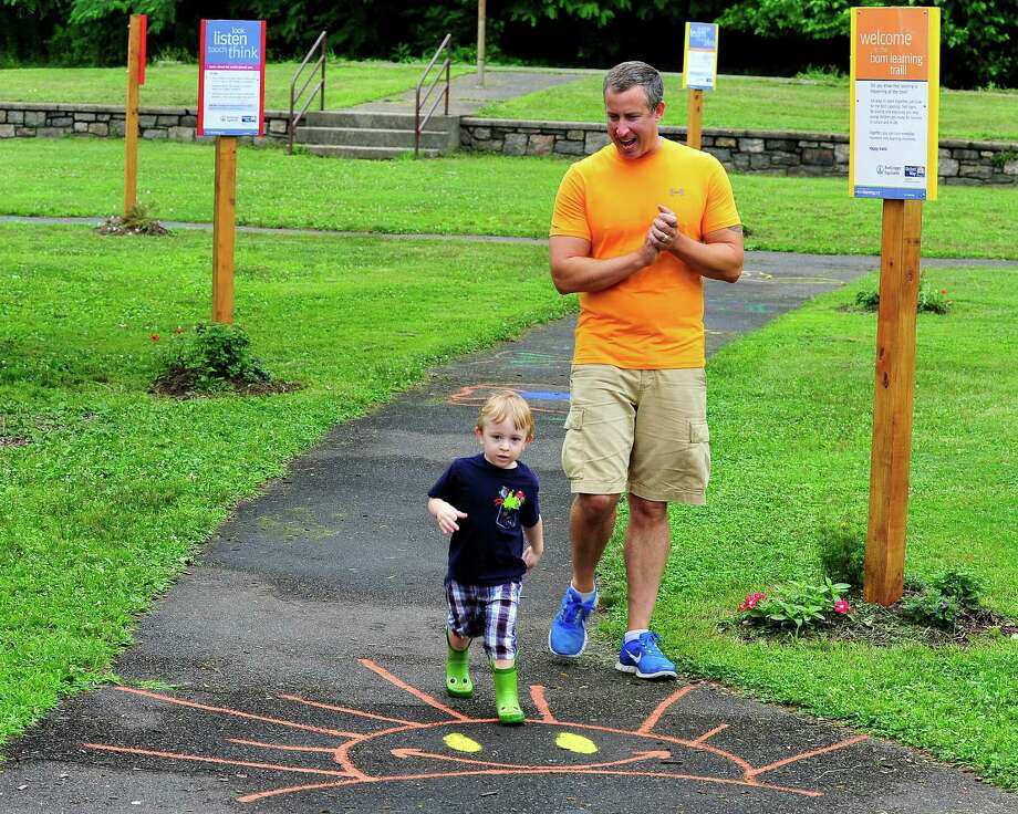 Sean Dean, 2, and his dad, John, of Bethel, enjoy the new Born Learning Trail at Rogers Park playground and spray park in Danbury, Conn. Saturday, July 13, 2013. Photo: Michael Duffy / The News-Times