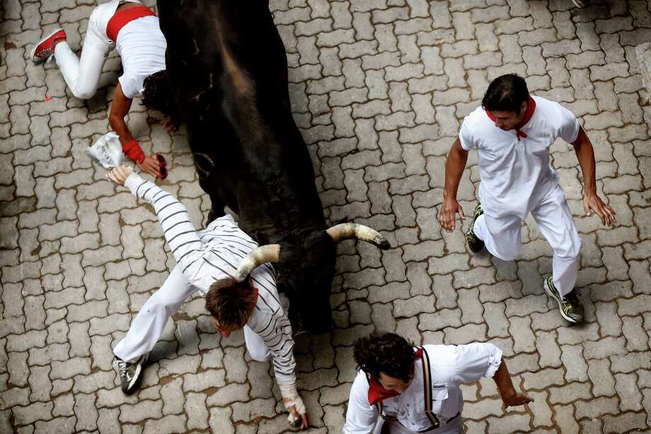 "Revelers are tossed by a Fuente Ymbro ranch fighting bull during the running of the bulls of the San Fermin festival, in Pamplona, Spain, Saturday, July 13, 2013. Revelers from around the world arrive in Pamplona every year to take part on some of the eight days of the running of the bulls glorified by Ernest Hemingway's 1926 novel ""The Sun Also Rises."" Photo: AP"